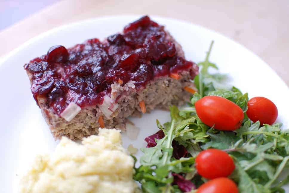 Cranberry chicken meatloaf on a plate next to mashed potatoes