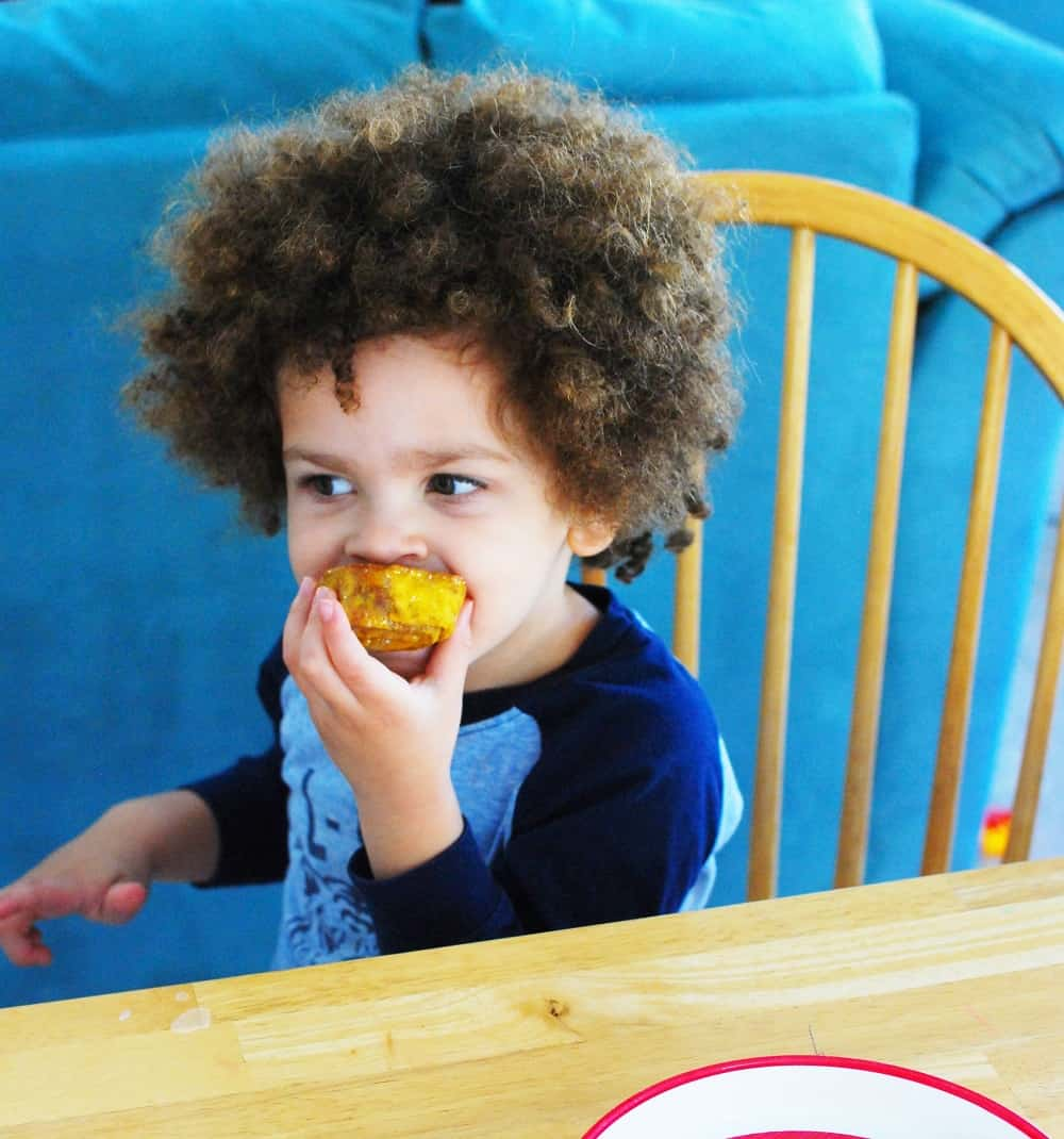 Child eating an easy pumpkin cinnamon roll