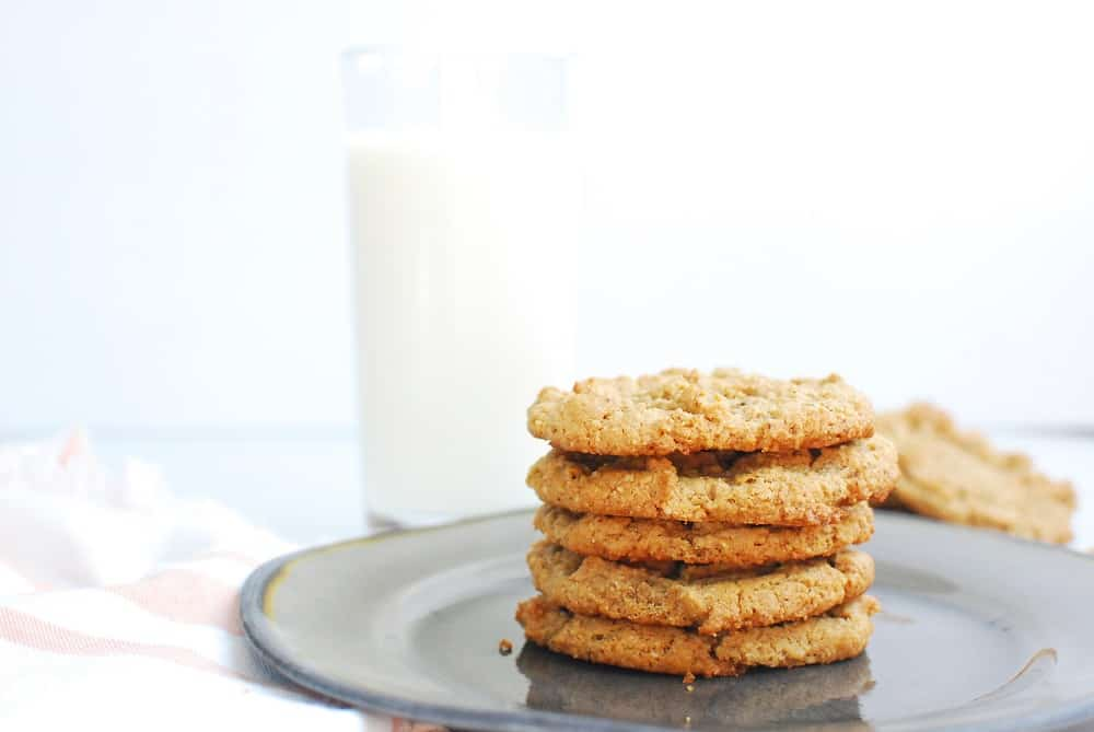 Stack of peanut butter cookies on a plate next to a glass of almond milk