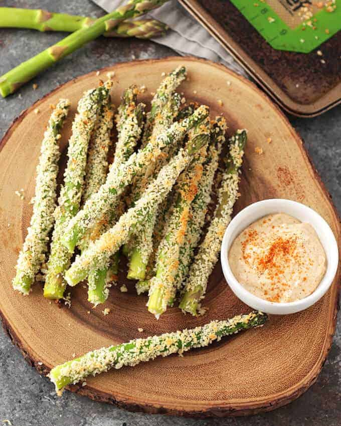 Dairy Free Baked Asparagus Fries on a bamboo platter with aioli sauce in a ramekin
