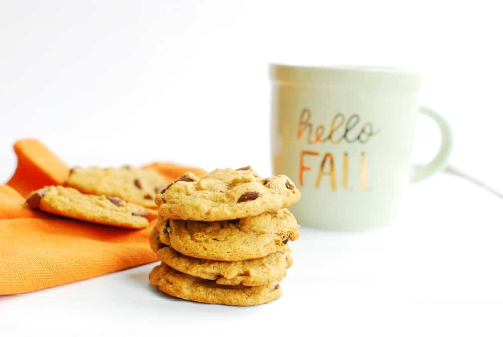 Several dairy free pumpkin chocolate chip cookies stacked up next to a fall mug