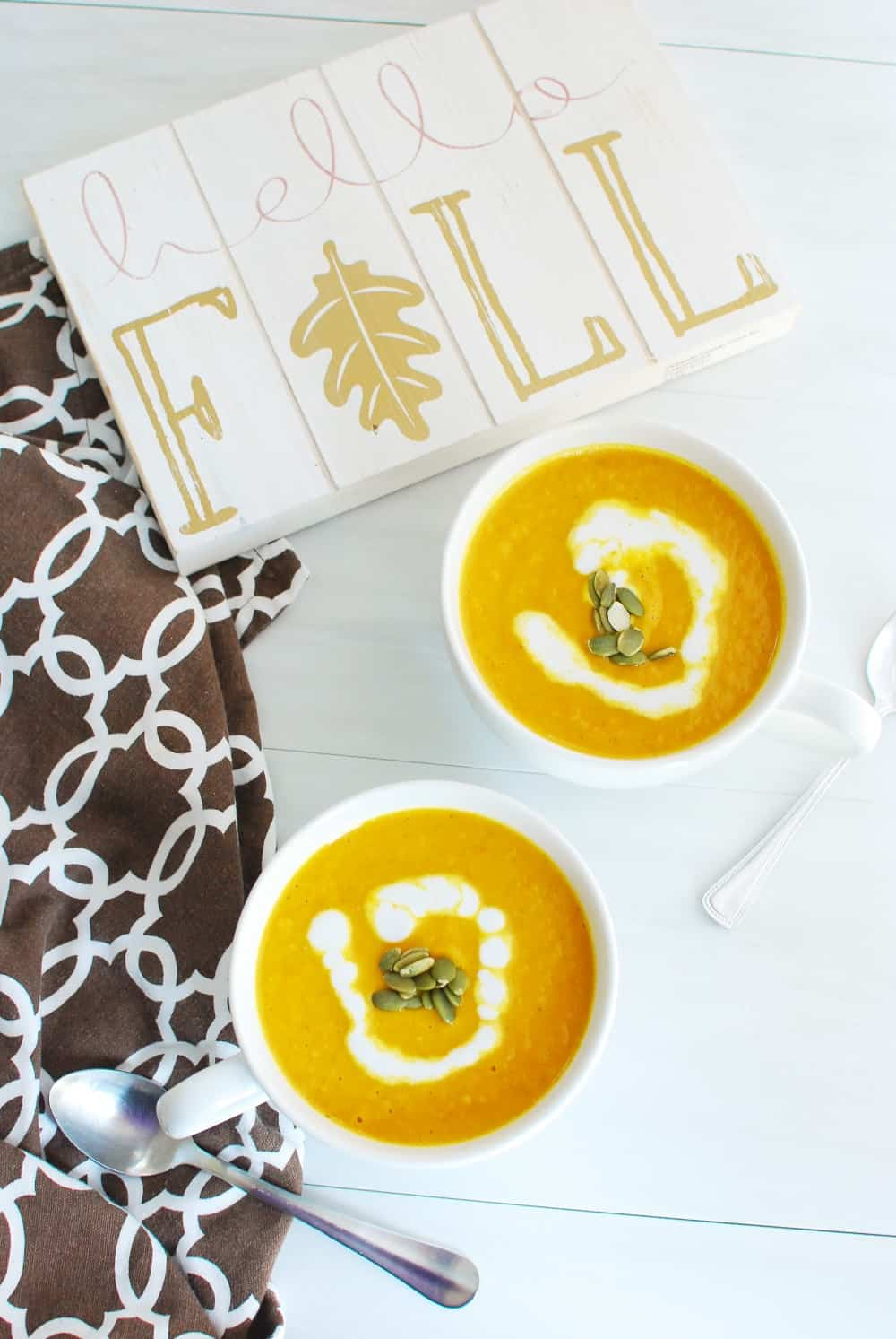 Two mugs full of vegan pumpkin soup next to a sign that says hello fall