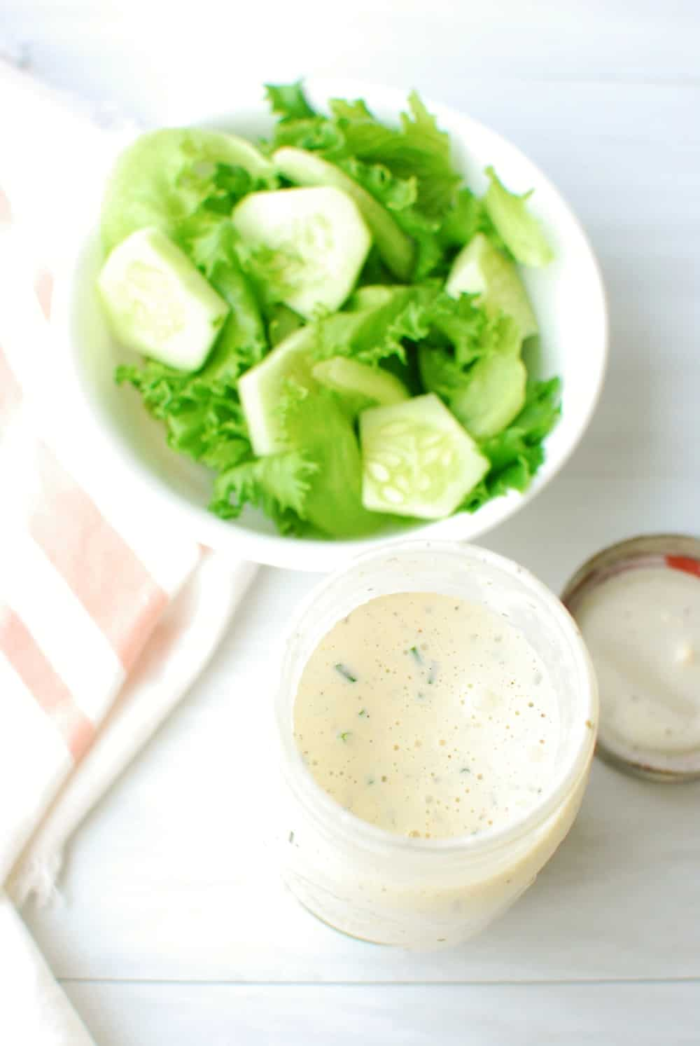 A jar of dairy free ranch dressing next to a bowl of salad
