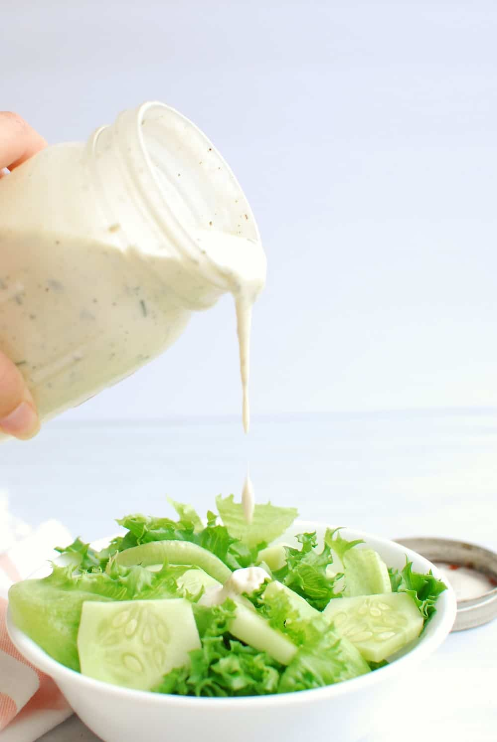 Pouring dressing over a salad with greens and cucumbers