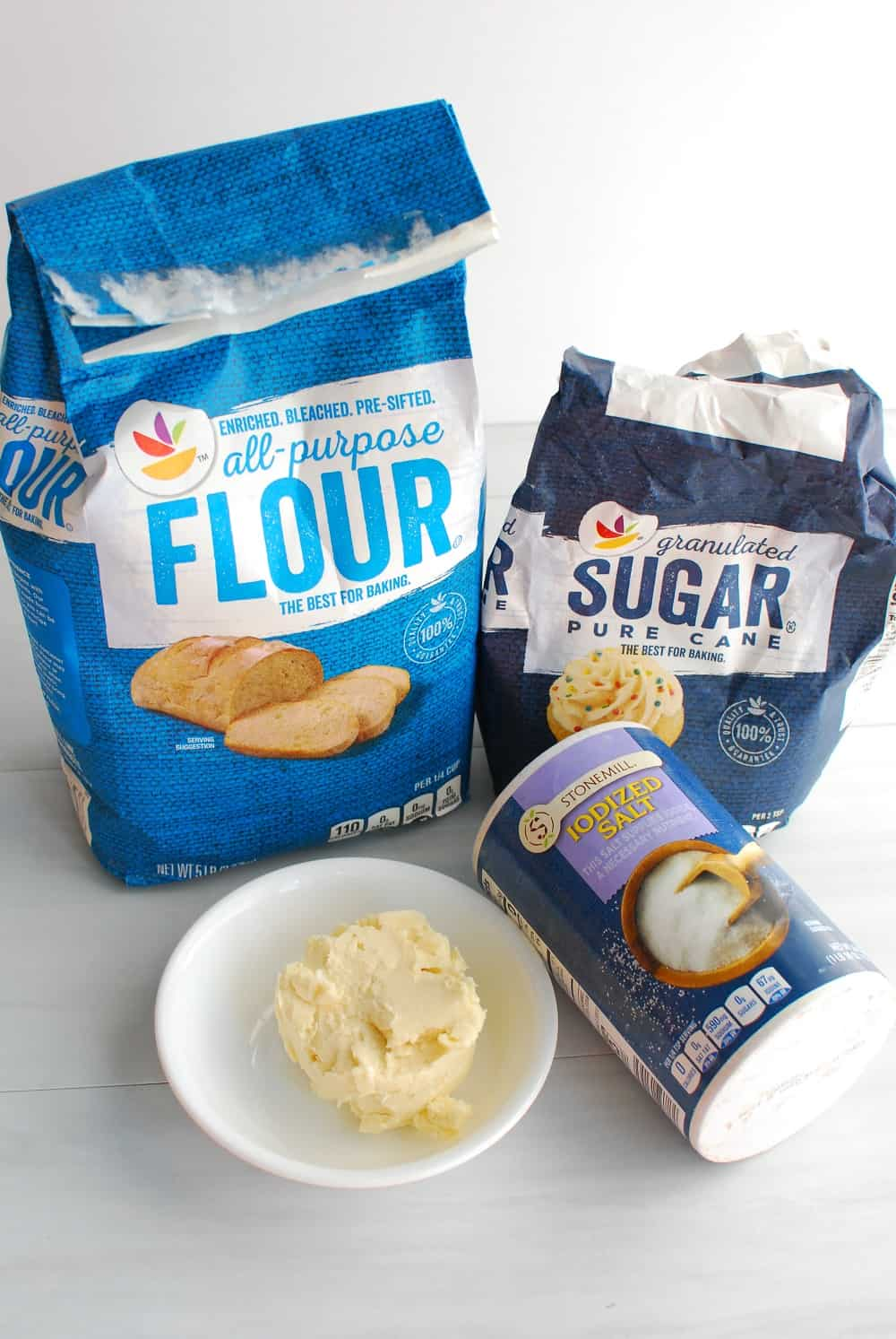 A bag of flour, a bowl of dairy free butter, a bag of sugar, and a canister of salt