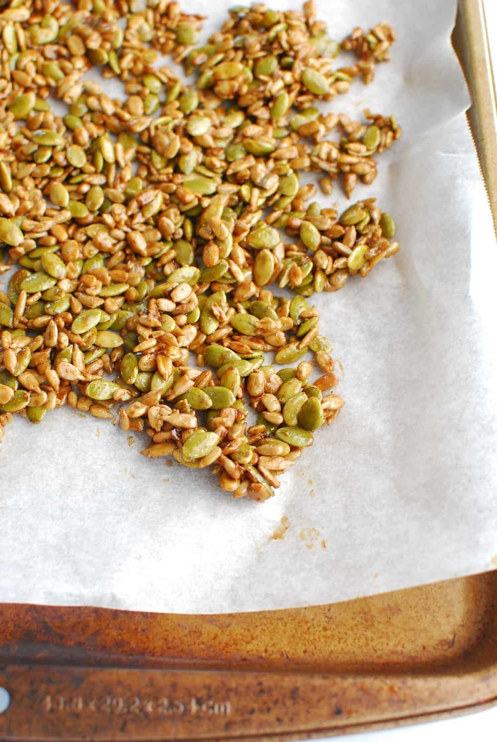 maple glazed pumpkin and sunflower seeds on a baking sheet