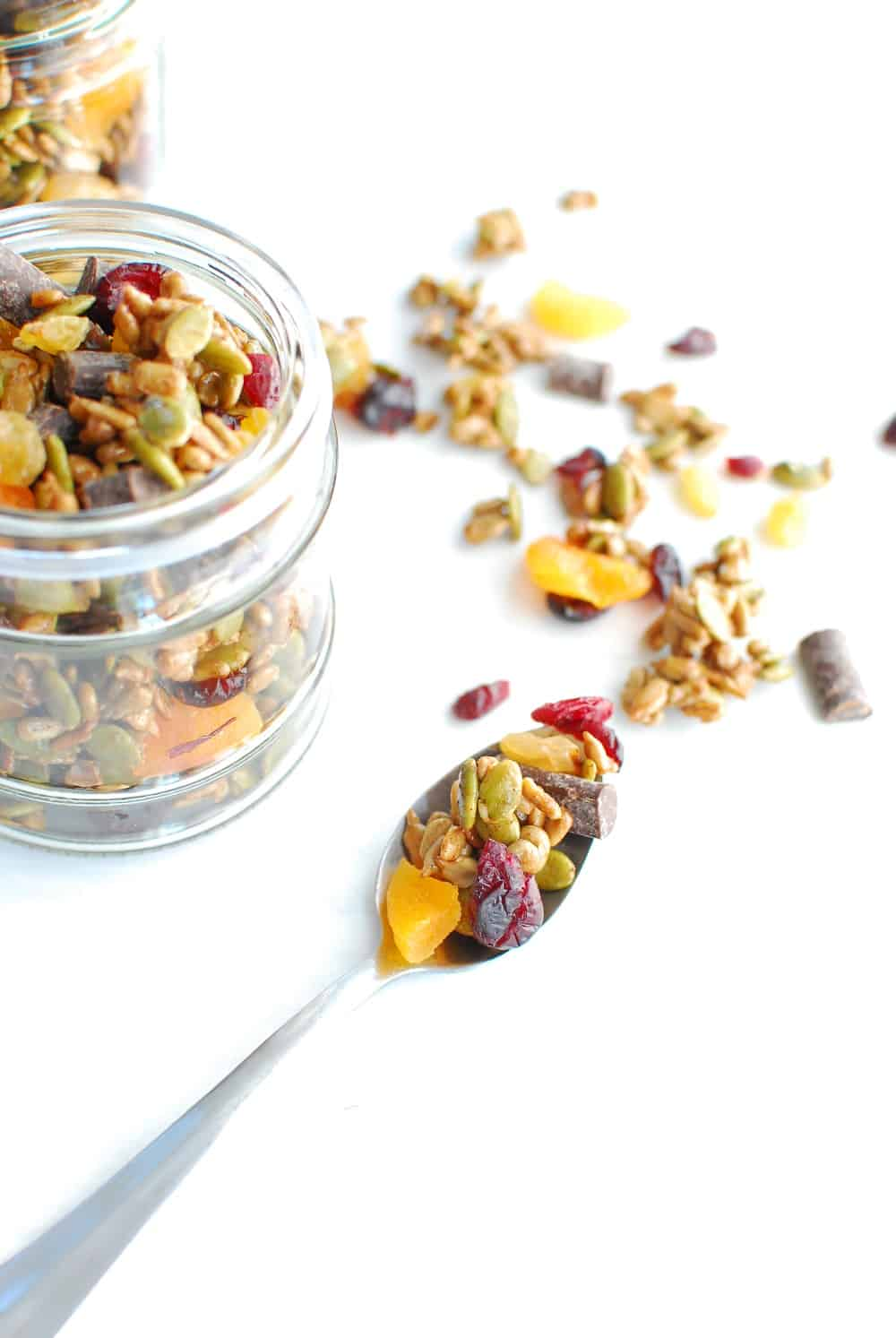 A spoonful of nut free trail mix next to a jar of it