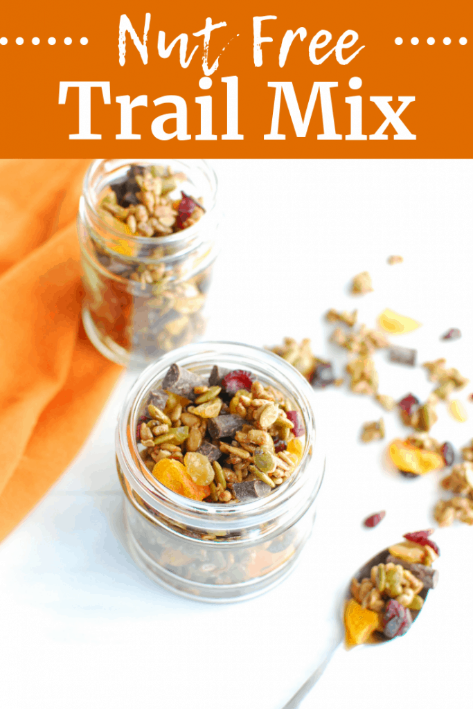 A jar of nut free trail mix next to an orange napkin