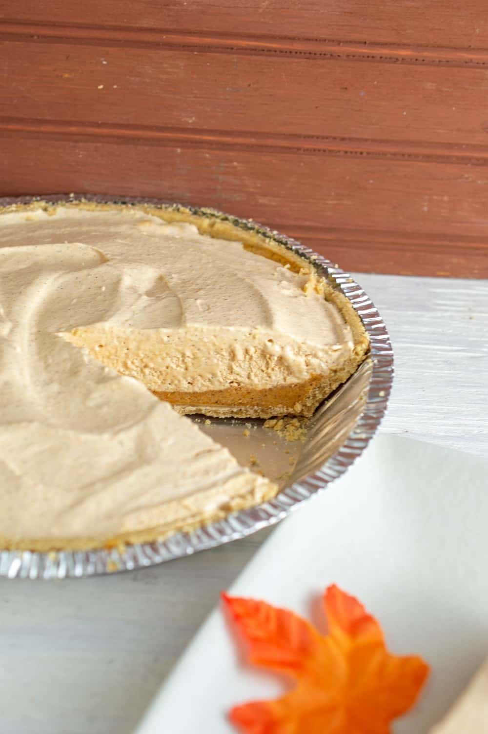 A dairy free pumpkin fluff pie with a slice removed
