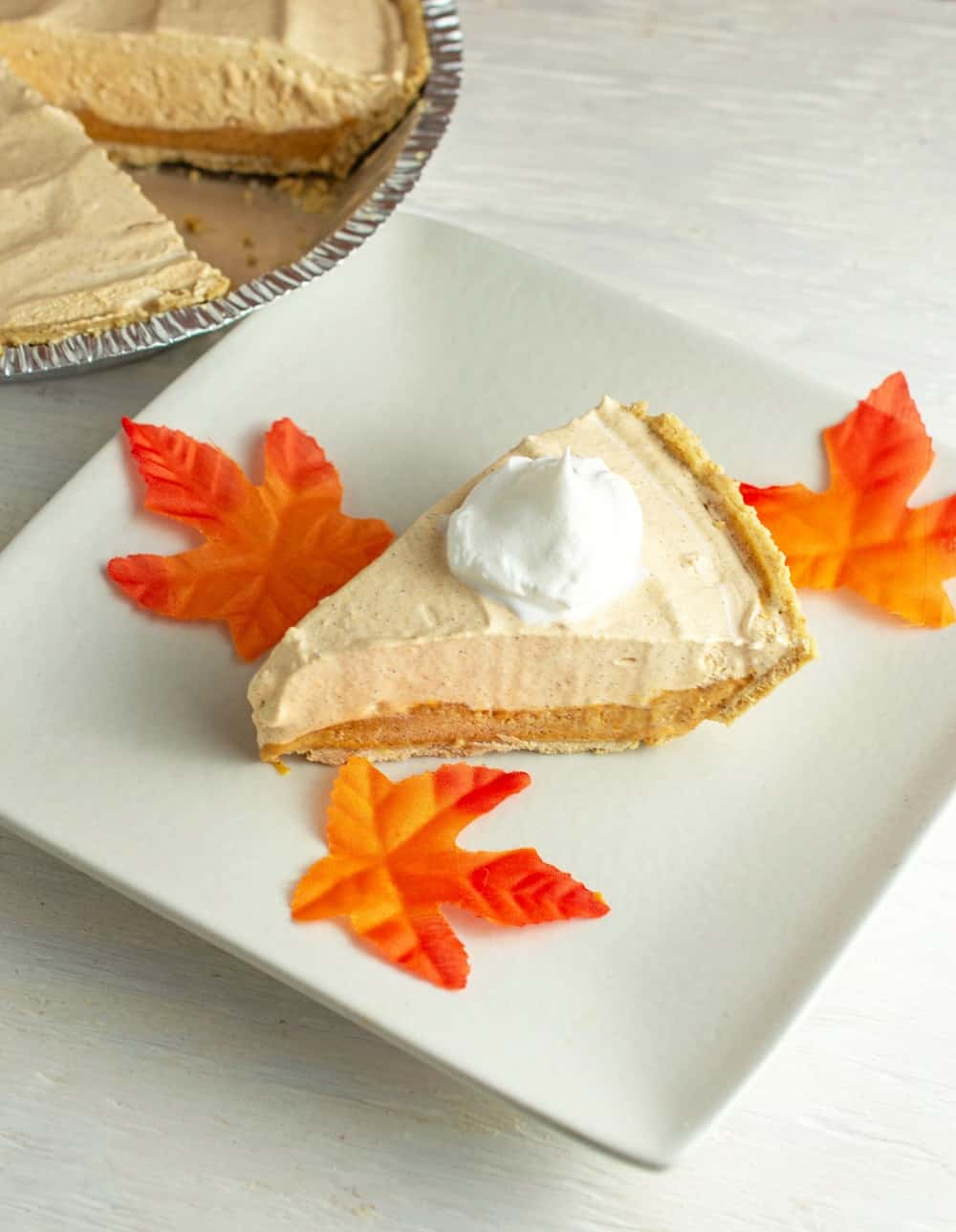 A slice of pumpkin fluff pie on a white plate