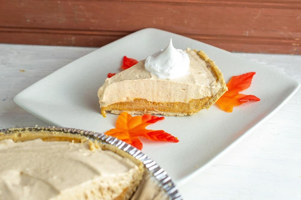A slice of pumpkin fluff pie on a plate next to some leaves