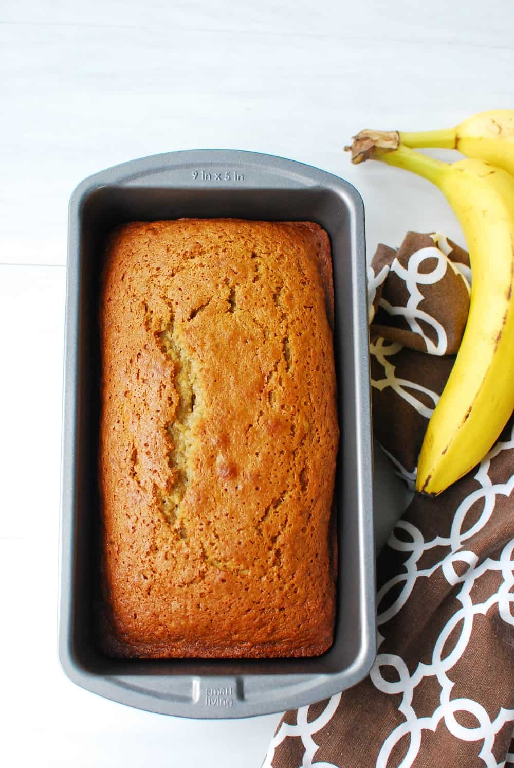 A loaf of dairy free banana bread in a loaf pan, just out of the oven