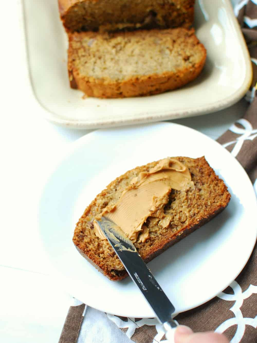 a woman spreading peanut butter onto a slice of banana bread