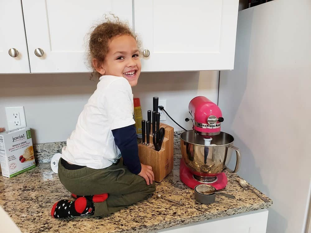 a child sitting next to a kitchenaid mixer