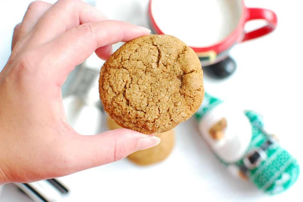 a woman holding a vegan gluten free gingersnap