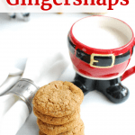 a stack of gingersnap cookies next to a glass of almond milk in a santa mug