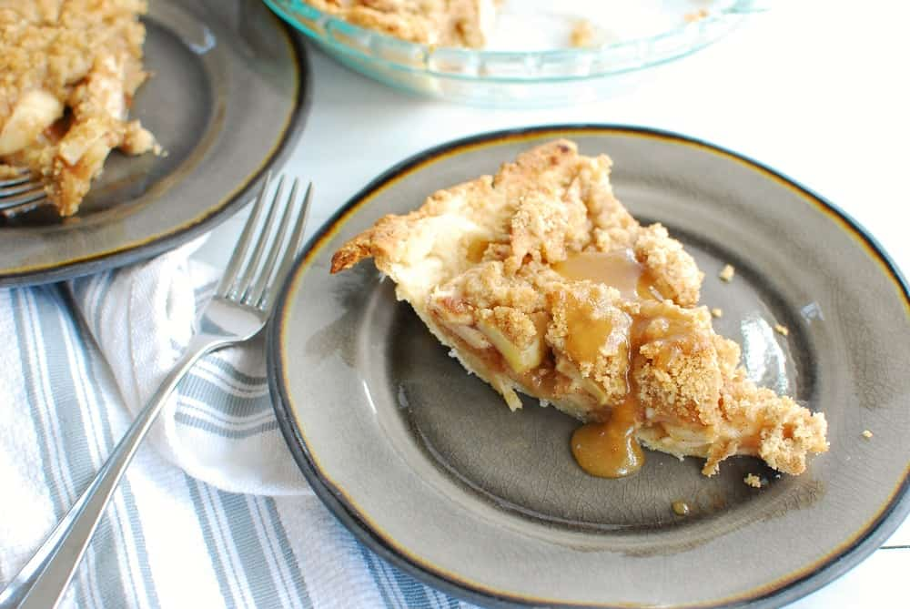 a slice of dairy free apple pie topped with caramel sauce
