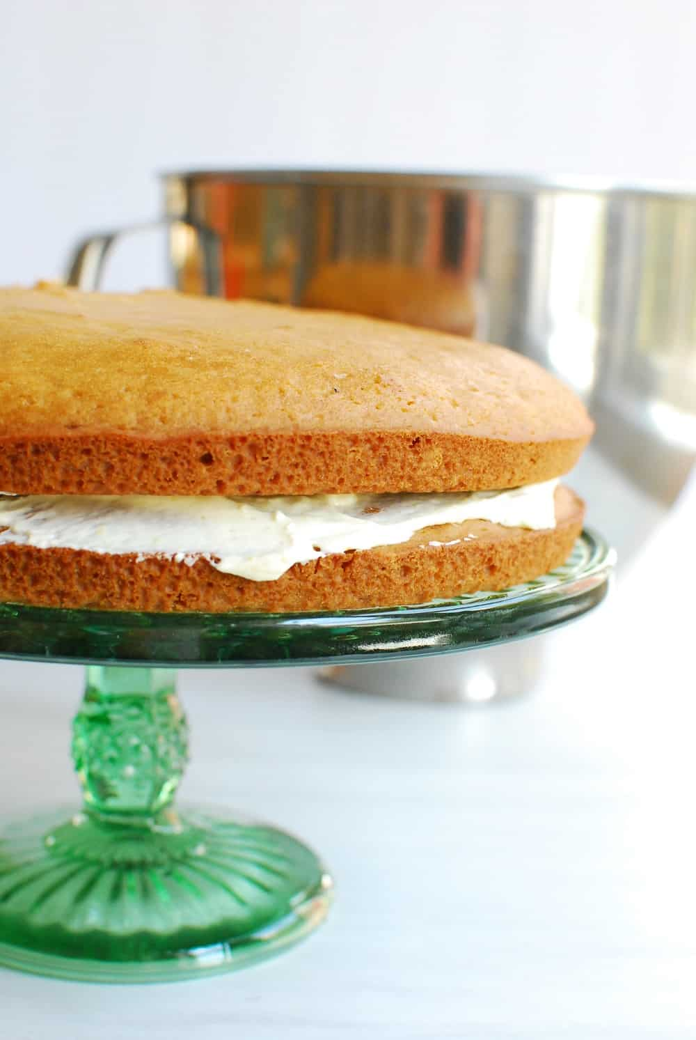 two cakes layered with frosting in the middle on a cake stand