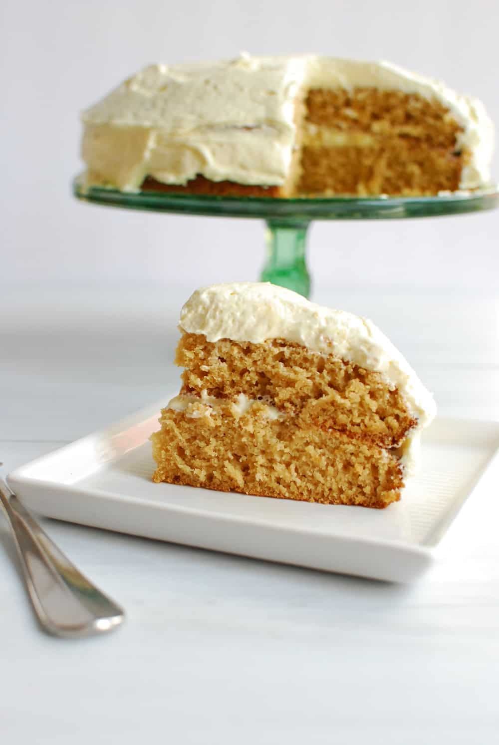 a slice of gluten free dairy free cake with vanilla frosting