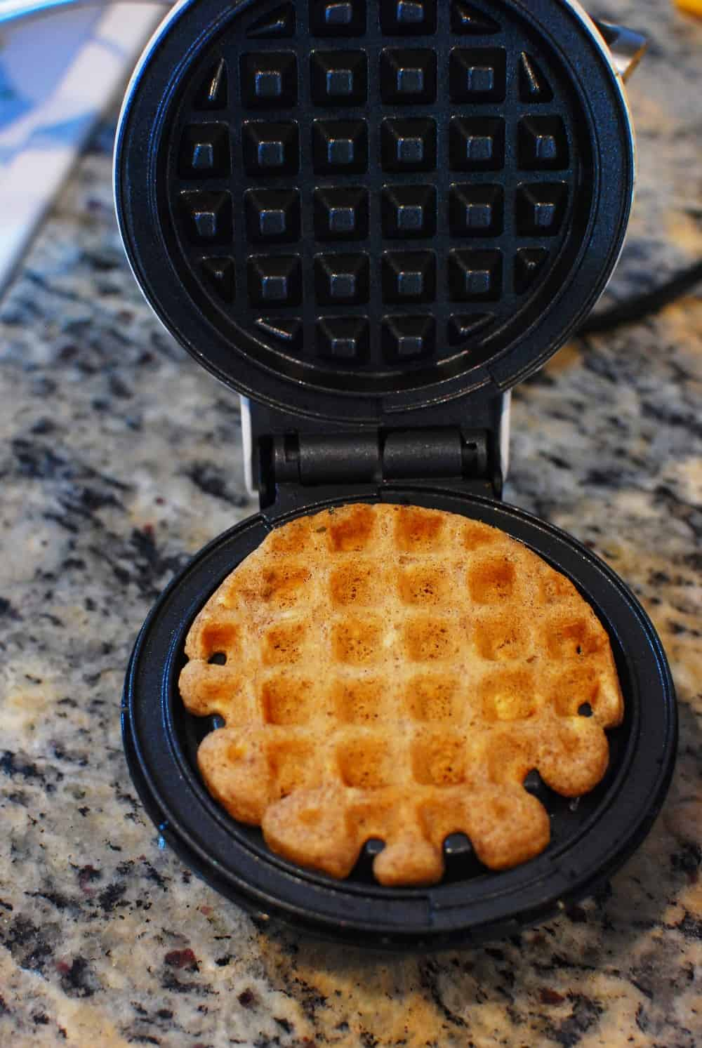 a waffle being cooked in a mini waffle maker