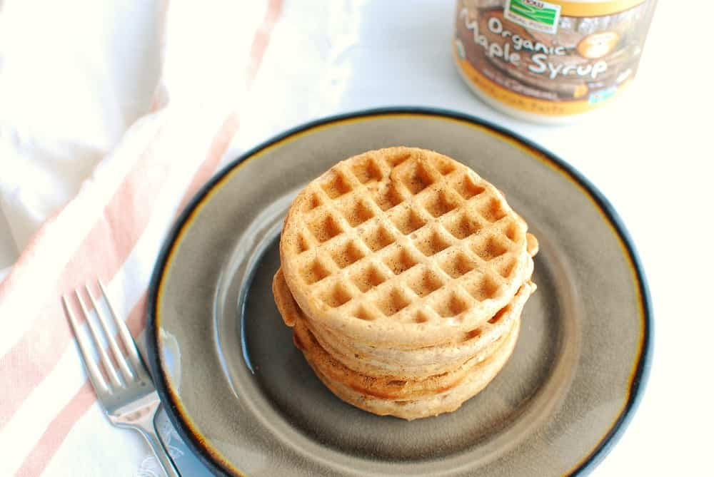 a stack of cinnamon waffles on a plate next to a fork