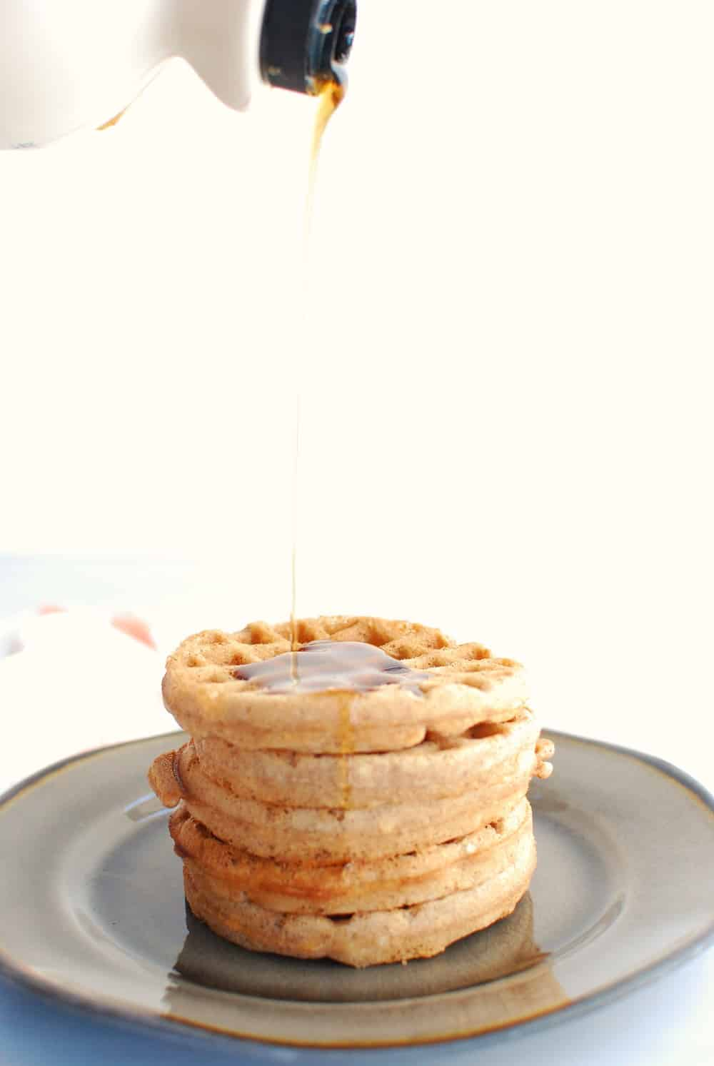 a stack of waffles with syrup being poured on top