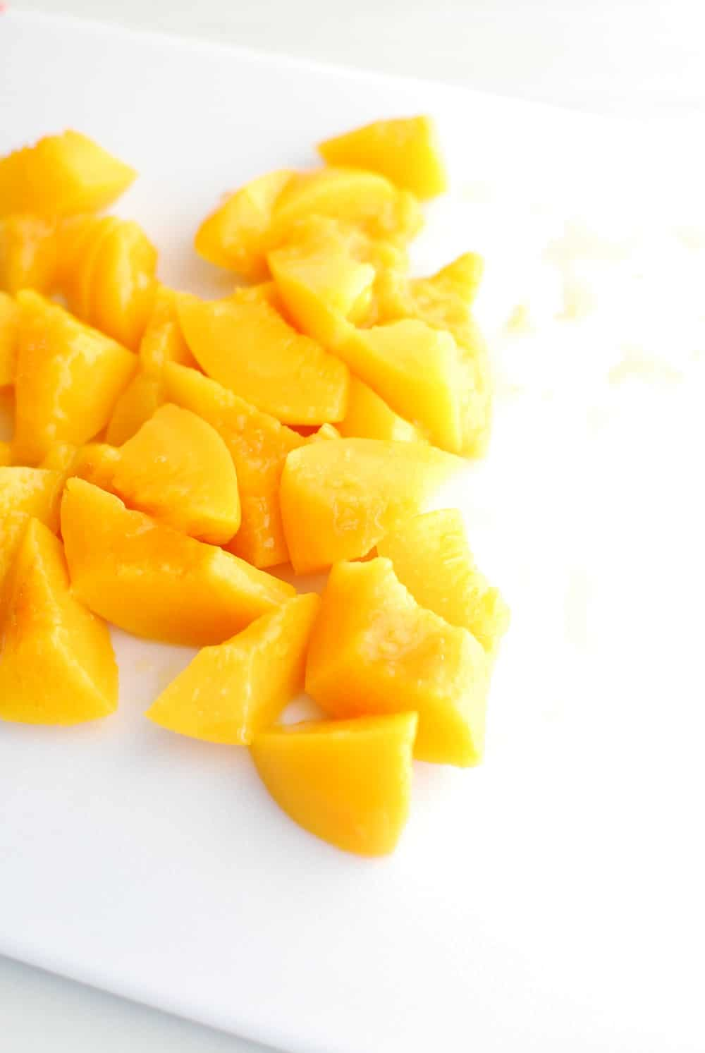 chopped up peaches on a cutting board