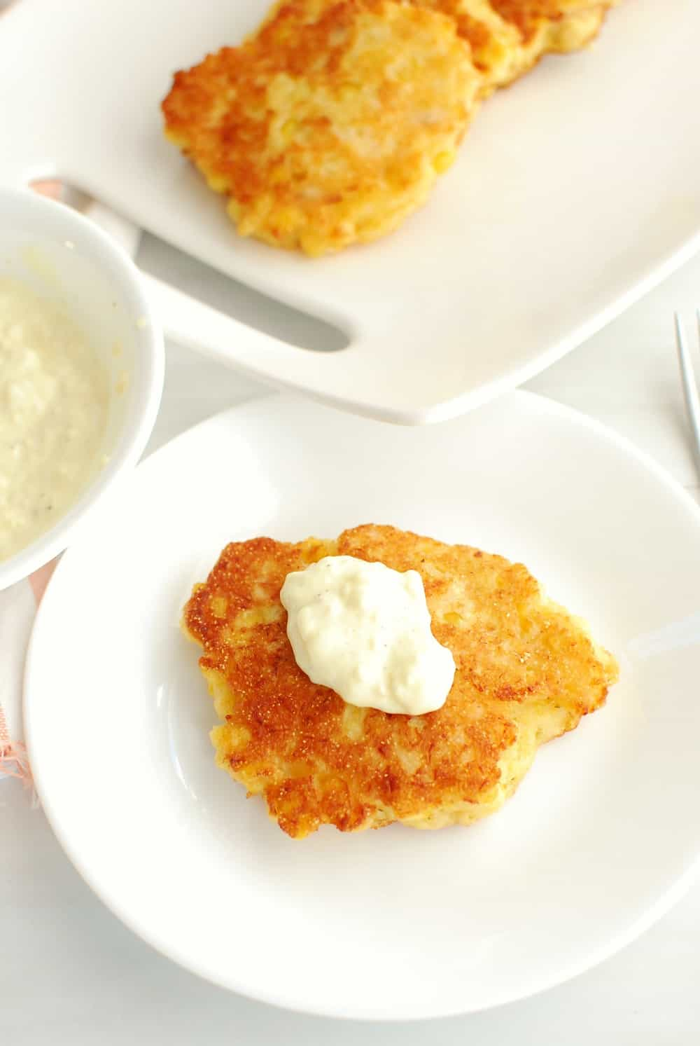 a salmon corn fritter on a white plate with a dollop of garlic mayo aioli