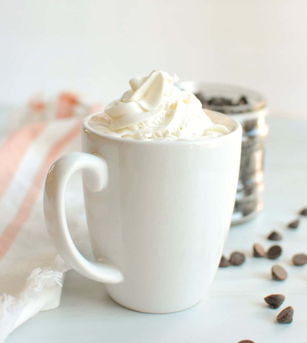 a mug of hot chocolate topped with dairy free whipped cream