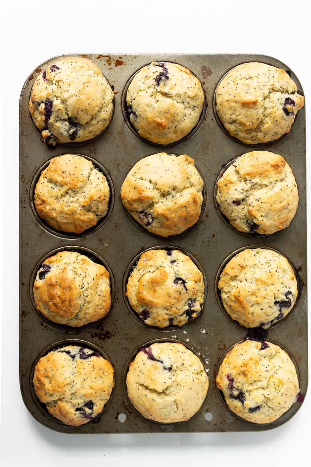 a muffin tin with just-baked dairy free lemon blueberry muffins