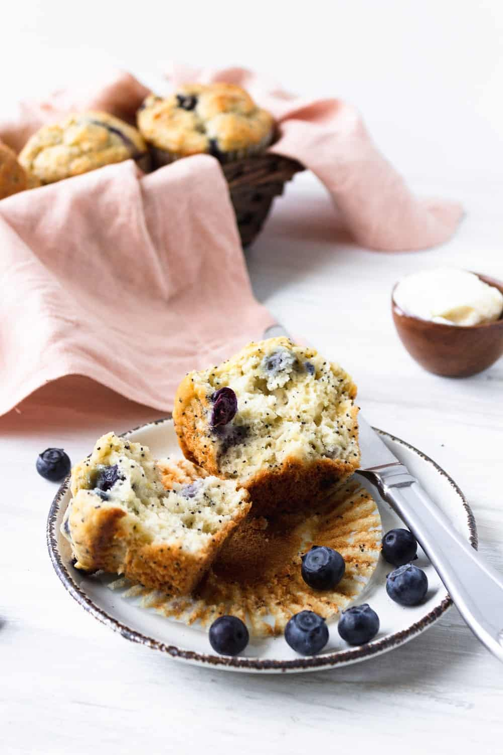 a dairy free blueberry muffin on a plate that's been cut in half