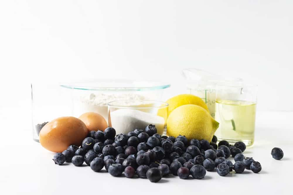 Ingredients for the recipe including blueberries, sugar, eggs, lemons, oil, and dairy free yogurt