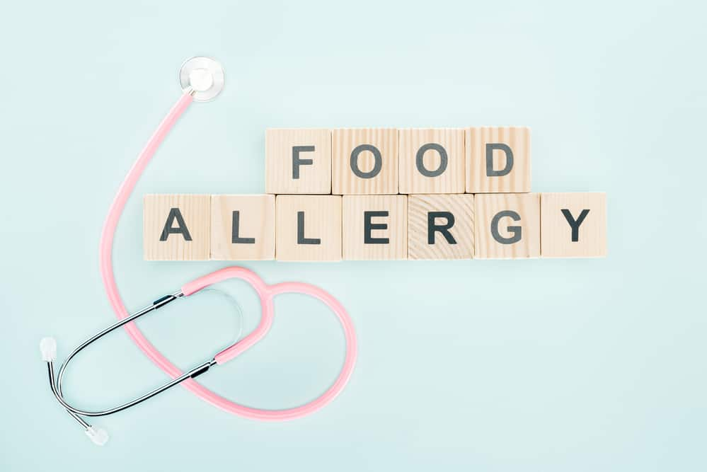 the word food allergy spelled out on some scrabble tiles, next to a stethescope
