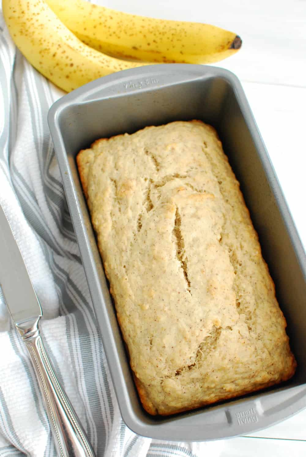5 ingredient vegan banana bread cooked in a loaf pan, next to a knife and two bananas