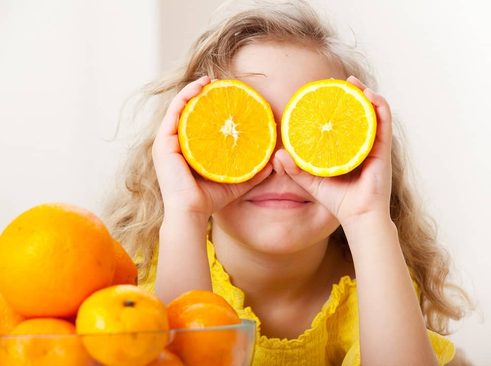 child holding orange slices up in front of her face