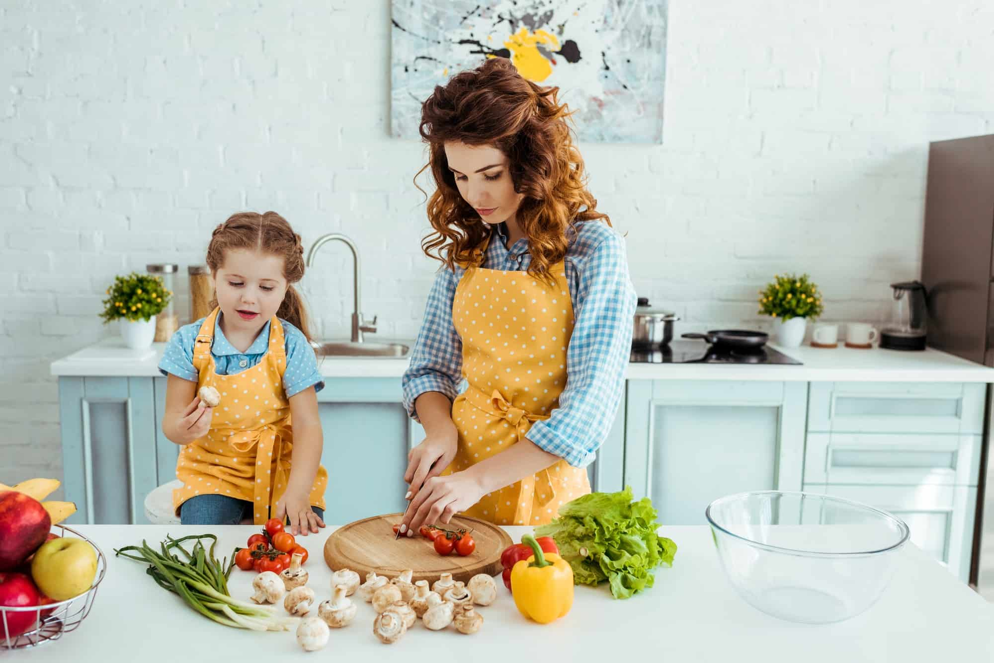a mother and child preparing vegetables together in the kitchen