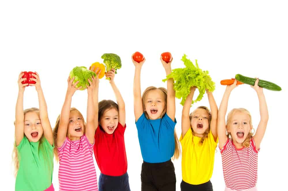 six children holding vegetables in their hands looking excited