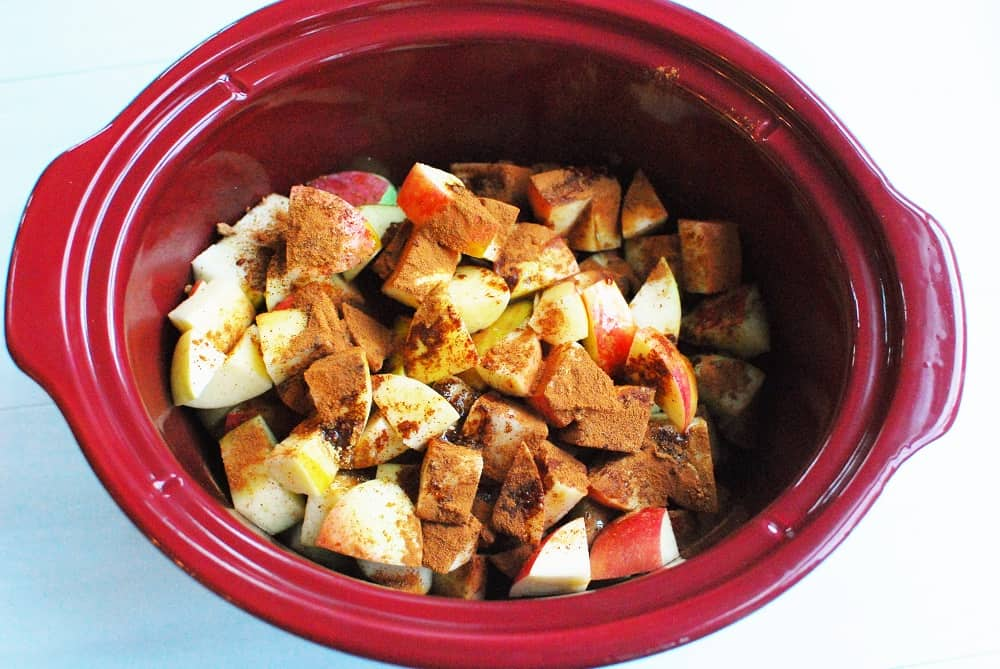 crockpot full of apples, spices, and maple syrup, before cooking