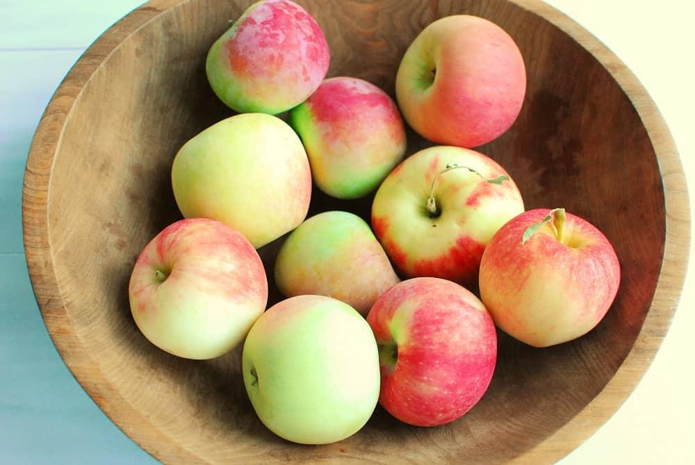a wooden bowl full of fresh apples