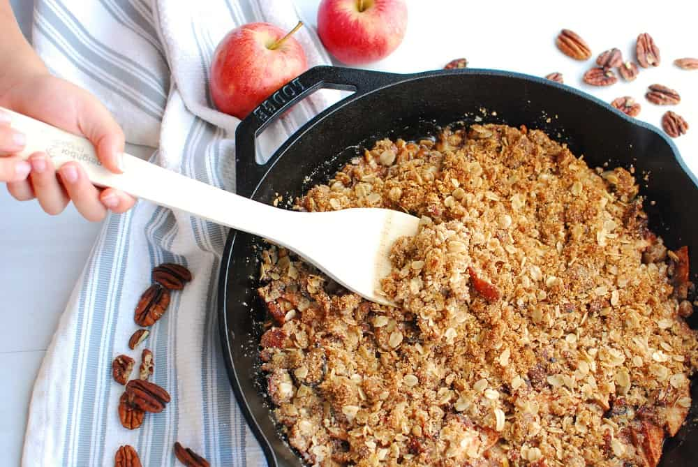 a wooden spoon scooping out some bacon apple crisp from a cast iron skillet