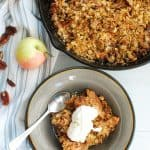 a bowl with bacon apple crisp and a spoon, next to a skillet full of the same