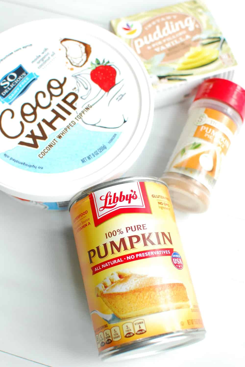 a can of pumpkin, a container of cocowhip, pumpkin spic, and vanilla pudding mx