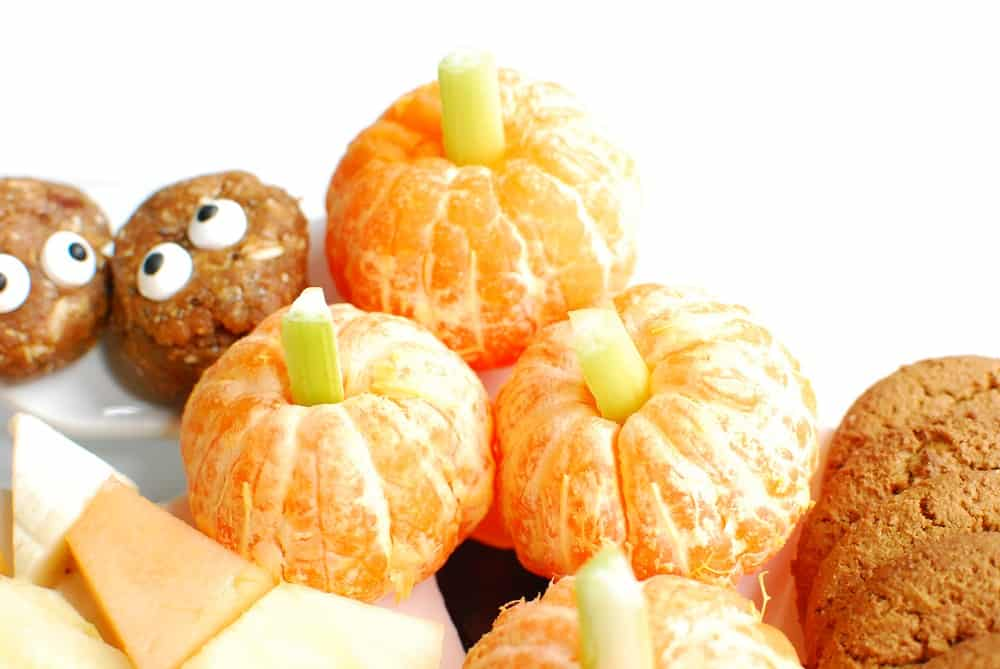 Clementines with a celery stalk in the middle that look like mini pumpkins