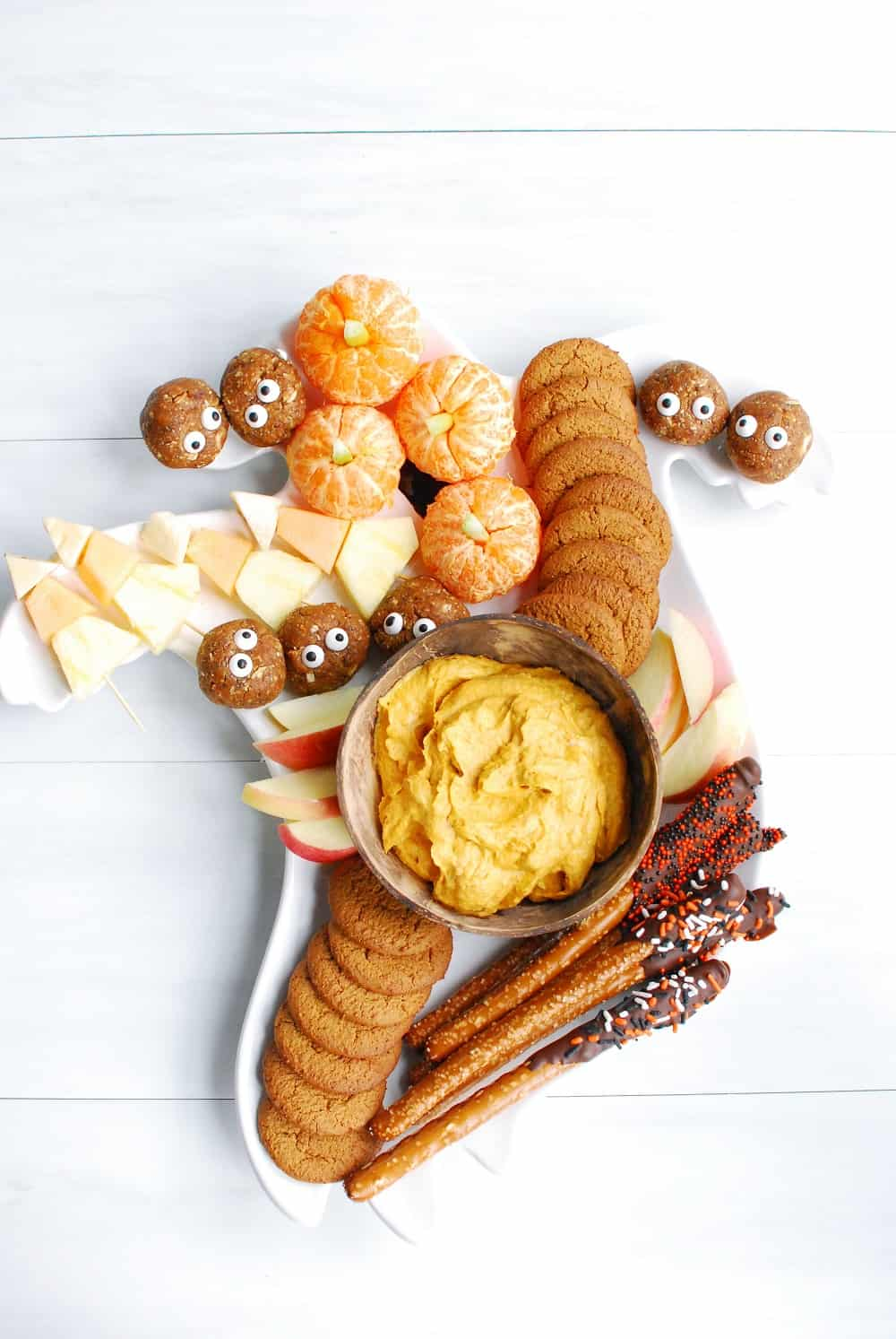 a Halloween charcuterie board filled with five different festive dessert treats, photographed vertically