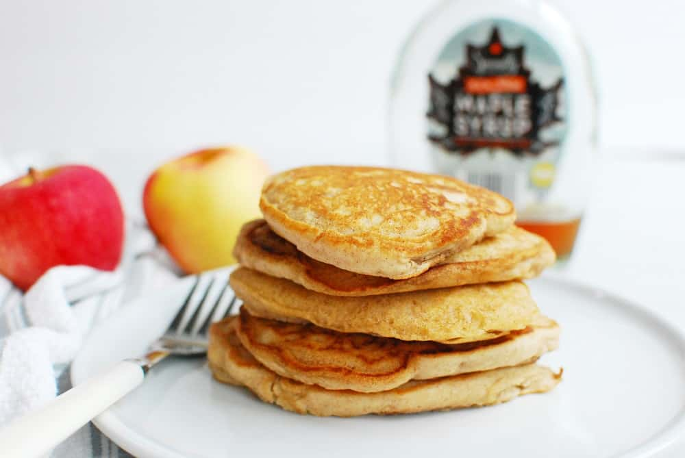 several vegan apple pancakes on a plate with a fork next to them