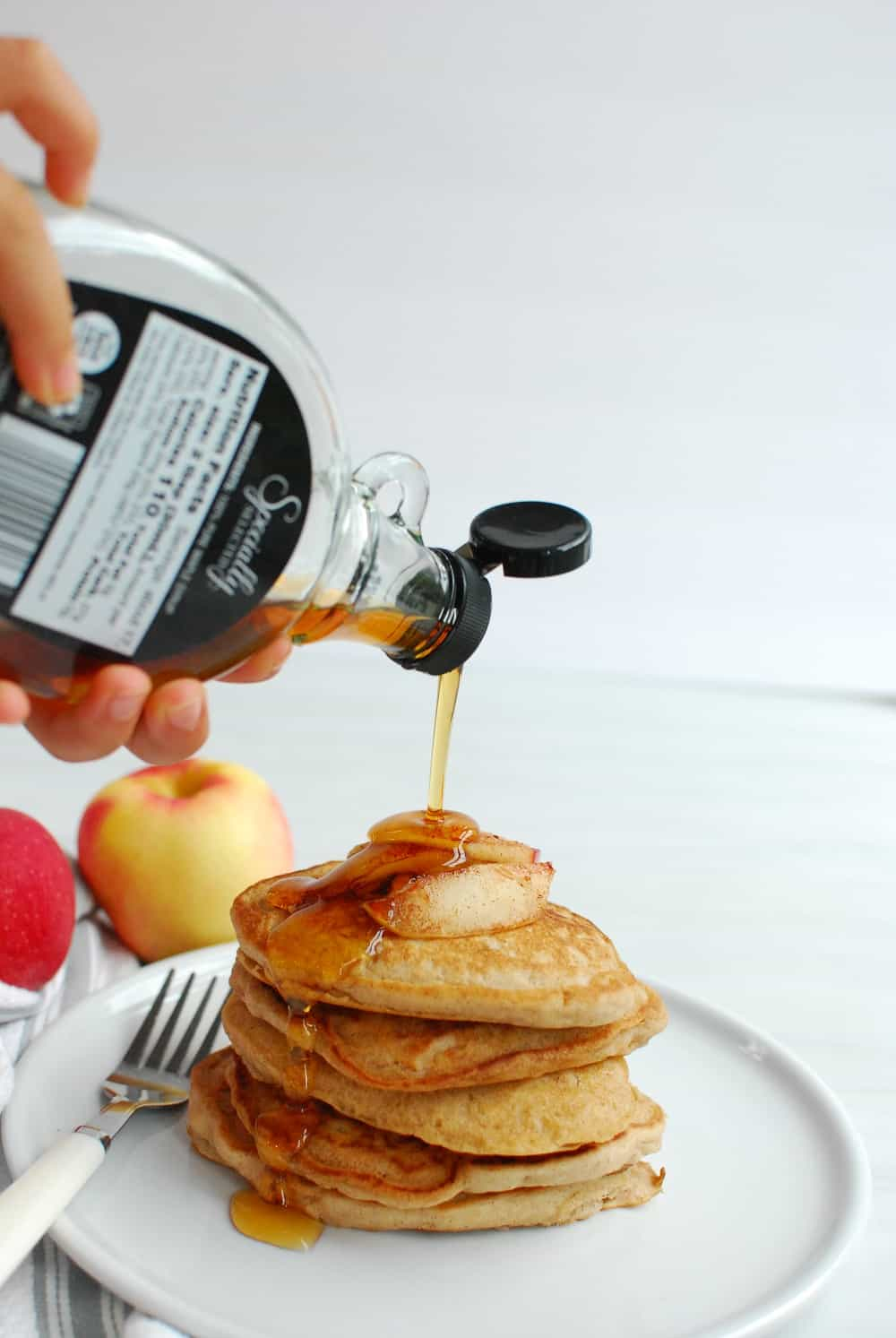 drizzling maple syrup over a stack of apple pancakes