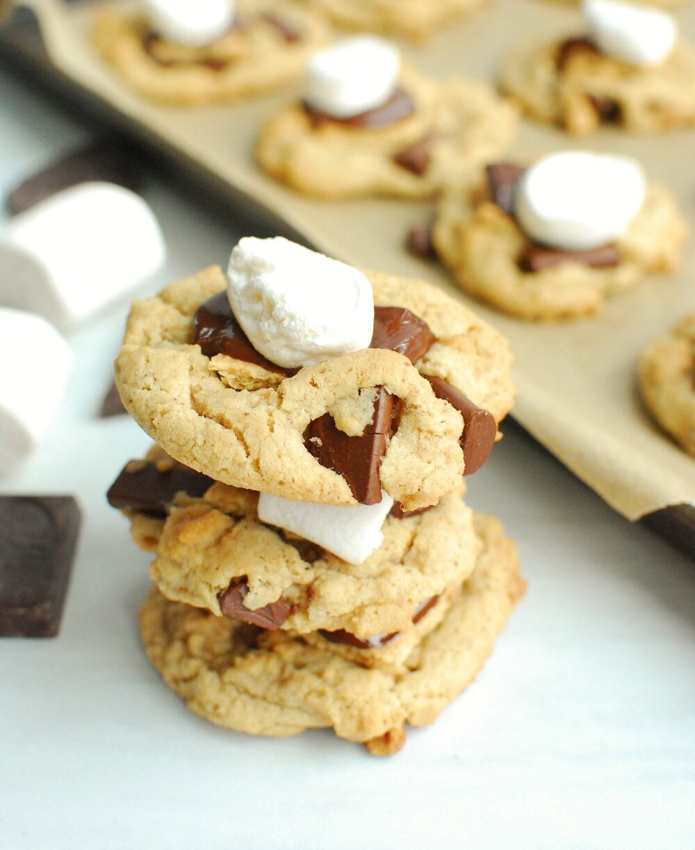 a stack of three vegan smores cookies next to some stray marshmallows and chocolate