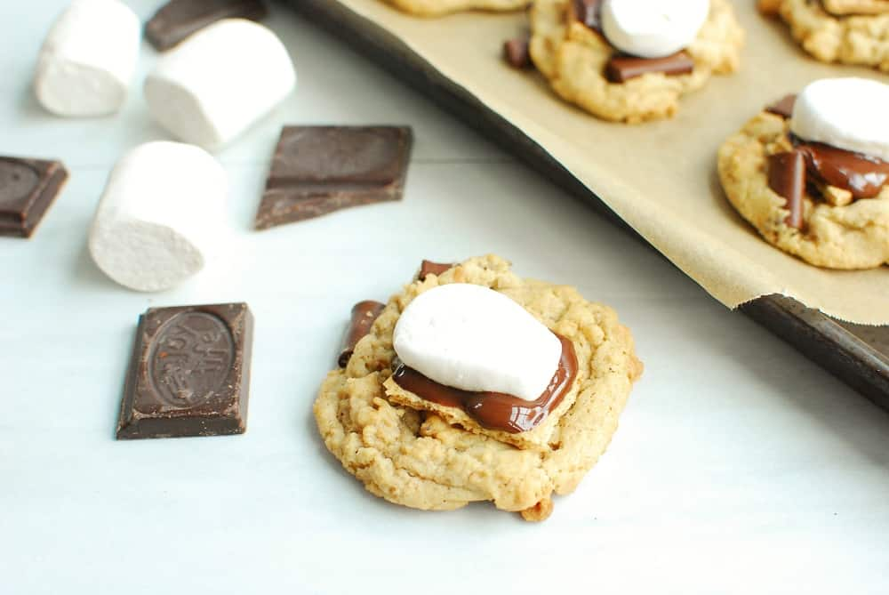 a dairy free smores cookie next to some chocolate and marshmallows