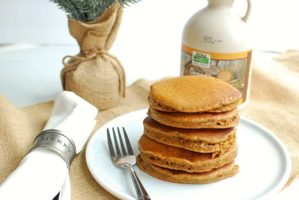 a stack of dairy free gingerbread pancakes on a white plate next to a napkin and a jug of maple syrup