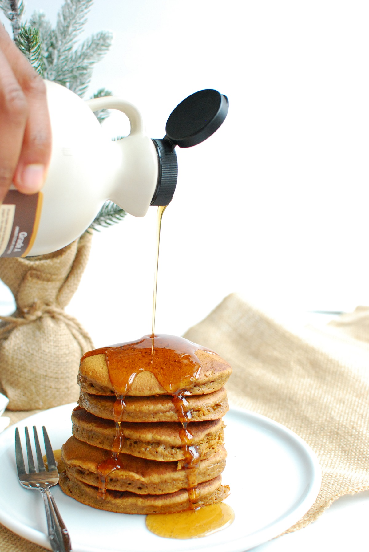 a man pouring syrup onto dairy free gingerbread pancakes
